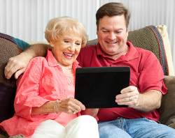son showing mother how to use tablet